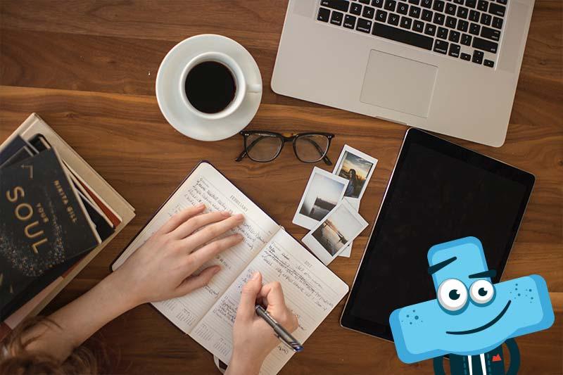 Laptop, tablet, notatnik, książki ikawa nabiurku.